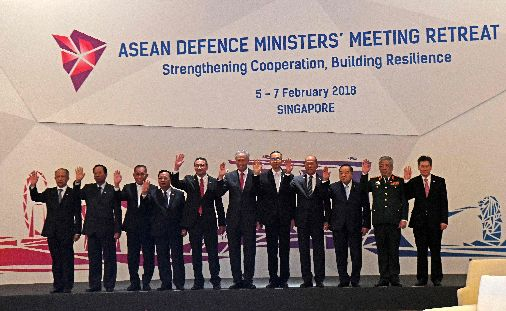 Association of Southeast Asian Nations (ASEAN) defence ministers (L to R) Brunei's Second Defence Minister Halbi Mohd Yusof, Cambodia's National Defence Minister Samdech Pichey Sena Tea Banh, Indonesian Defence Minister Ryamizard Ryacudu, Laotian Defence Minister Chansomone Chanyalath, Malaysian Defence Minister Hishammuddin Tun Hussein, Singapore's Defence Minister Ng Eng Hen, Myanmar's Defence Minister Sein Win, Philippine Defence Secretary Delfin N. Lorenzana, Thailand's Defence Minister Prawit Wongsuwan, Vietnam's Deputy Defence Minister Nguyen Chi Vinh, and ASEAN Secretary-General Lim Jock Hoi wave during a group photo at the ASEAN defence ministers' meeting in Singapore on February 6, 2018. / AFP PHOTO / ROSLAN RAHMAN